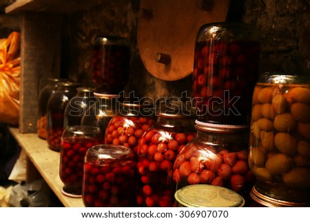 Home preservation in glass jars in cellar, closeup - stock photo