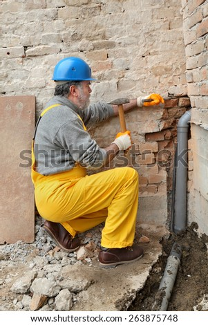 Home renovation, plumber install sewerage pipe at construction site using hammer and chisel - stock photo