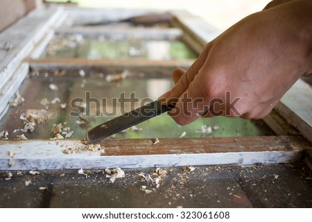 Home Renovation, woman's hand removing a white paint from a wooden Window with a Scraper - stock photo