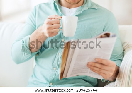home, rest, news, drinks and people concept - close up of man reading magazine and drinking from cup sitting on couch at home - stock photo