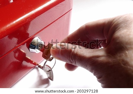 Home safe box with hand turning key in lock. - stock photo
