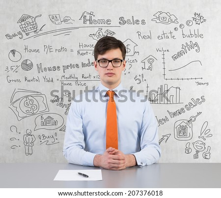 Home sales wall and sitting businessman with a blank paper and a pen.