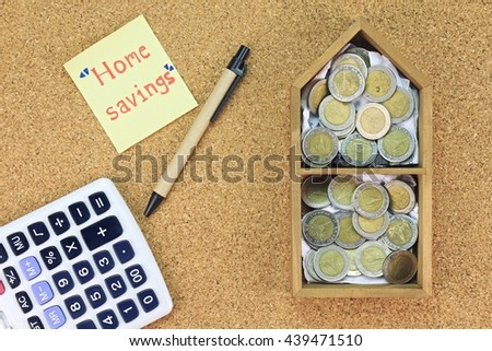 Home saving concept, Money saving for dream home. Model house and coins on wood board. Calculate for home budget. - stock photo