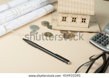 Home savings, budget concept. Model house, notepade, pen, calculator and coins on wooden office desk table - stock photo