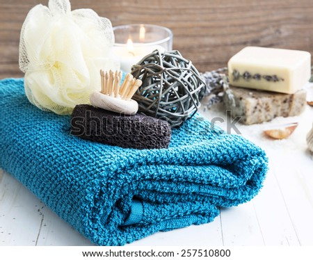 Home-Spa Products with Cotton Towel,Pumice and Body Brush and Natural Soaps in the Background