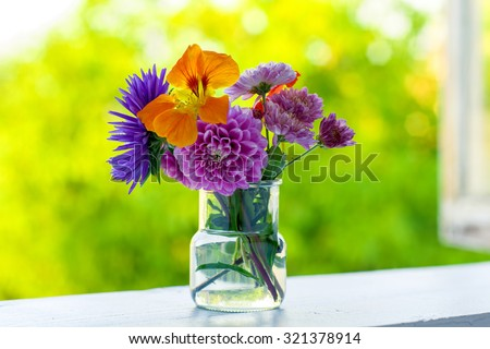 Home style fall bouquet with garden flowers on the window sill in the sunshine. Shallow DOF. Horizontal composition. - stock photo