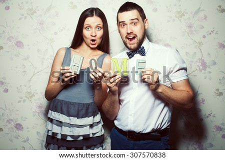 Home sweet home concept. Portrait of funny, happy couple of hipsters (husband and wife) in trendy clothes holding letters H O M E. Casual, vintage style. Studio shot
