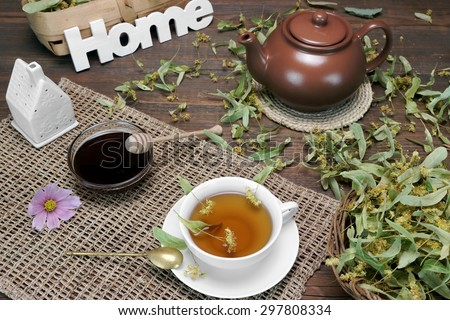 Home Tea Time Scene. Tea Cup With Lime Tree Herbal Green Tea, Honey, Herbs Leafs In The Basket, Clay Teapot, Vintage Spoon And Sign Home On Rustic Old Wooden Table - stock photo