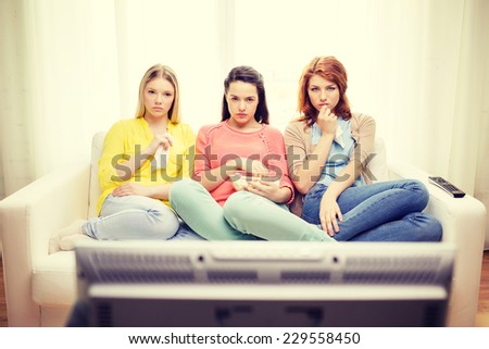 home, technology and friendship concept - three sad teenage girl watching tv at home and eating popcorn - stock photo