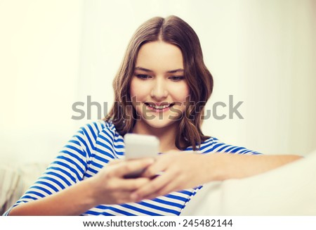 home, technology and internet concept - smiling teenage girl with smartphone sitting on couch at home - stock photo