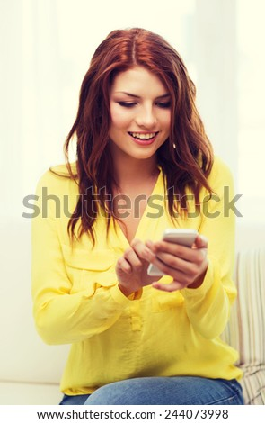home, technology and internet concept - smiling woman with smartphone sitting on couch at home - stock photo