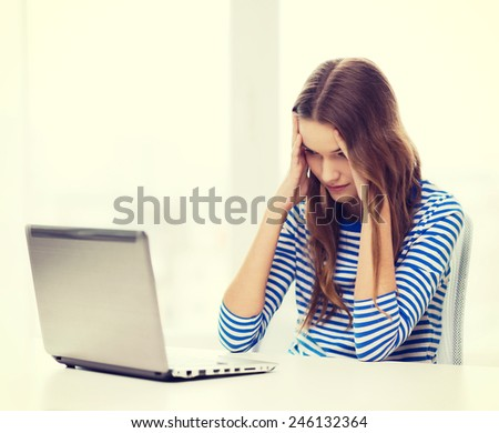 home, technology and internet concept - upset teenage girl with laptop computer at home - stock photo