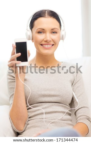 home, technology, communication and internet concept - woman sitting on the couch with smartphone and headphones at home