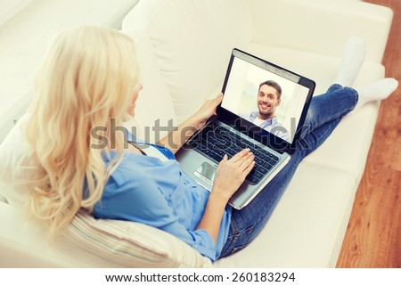 home, technology, communication and people concept - smiling woman sitting on couch and chatting with laptop computer at home - stock photo