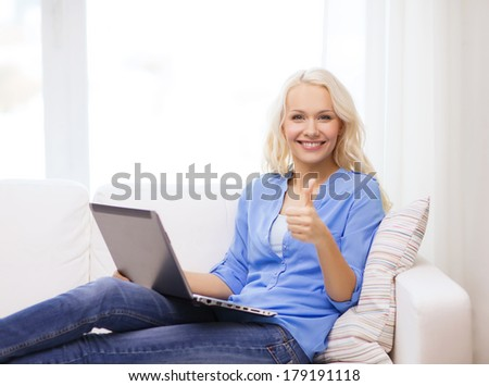 home, technology, gesture and internet concept - smiling woman sitting on the couch with laptop computer at home showing thumbs up - stock photo