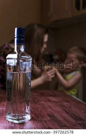 Home violence: Drunk woman and her little child in kitchen. Alcoholic addiction. Focus on bottle. - stock photo