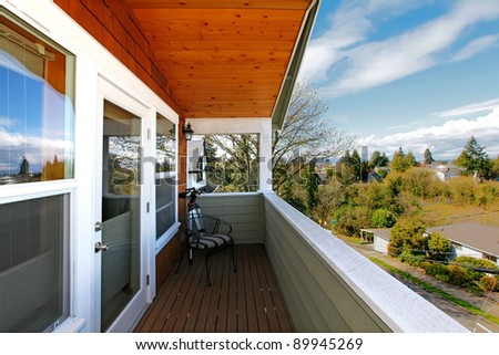 Home with covered balcony with wood ceiling and view of Seattle's neighborhood.