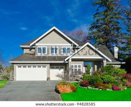 Home with covered entry and double three car garage with the dark blue sky in the autumn time of the year. Vancouver.
