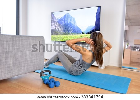 Home workout - woman exercising in front of a flat screen watching a fitness program or exercising during a TV show lying on a yoga mat in front of the sofa in the living room of a house or apartment. - stock photo