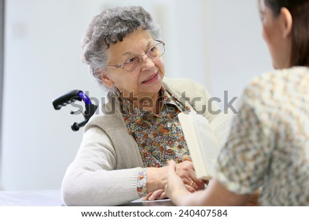 Homec arer reading book to old woman in nursing home - stock photo