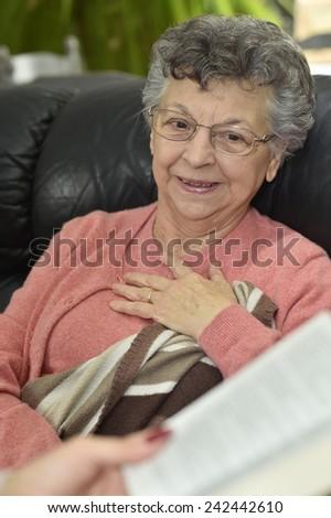 Homecare reading book to elderly woman - stock photo