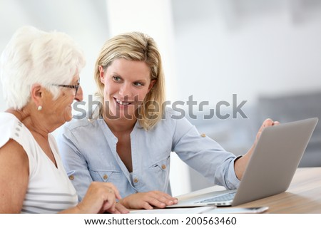 Homecarer with elderly woman using laptop computer - stock photo
