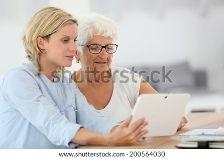 Homehelp with elderly woman using digital tablet - stock photo