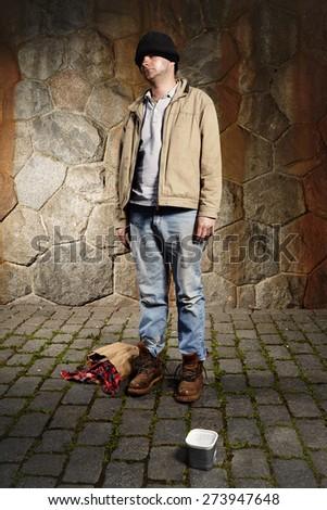 Homeless beggar asking for some coins on sidewalk - stock photo