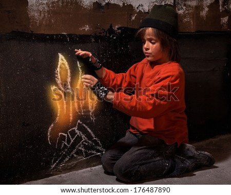 Homeless boy warming at virtual drawn fire kneeling near a wall - social issues concept - stock photo