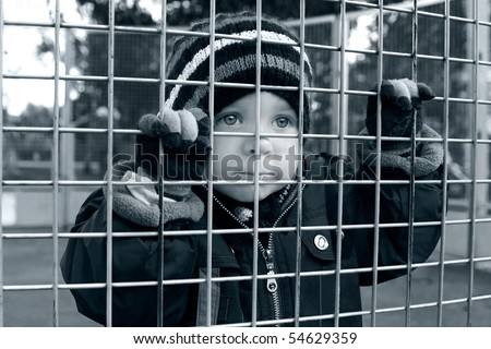 homeless child looking through fence, bored boy - stock photo
