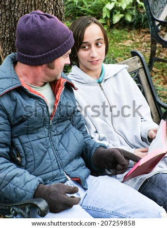 Homeless father and son reading the Bible, or a teen volunteer ministering to the poor.   - stock photo