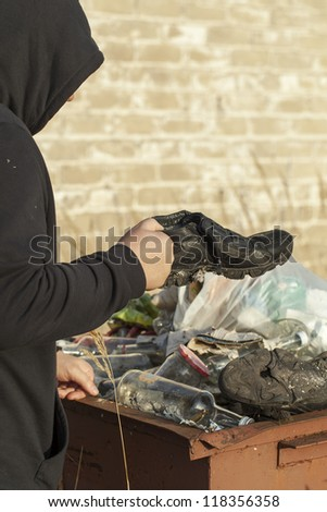 Homeless find the footwear in waste container - stock photo