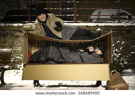 Homeless friends living in paper box on bench in winter park - stock photo
