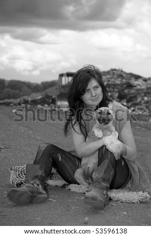 Homeless girl searches for ways of a survival on a city dump. - stock photo