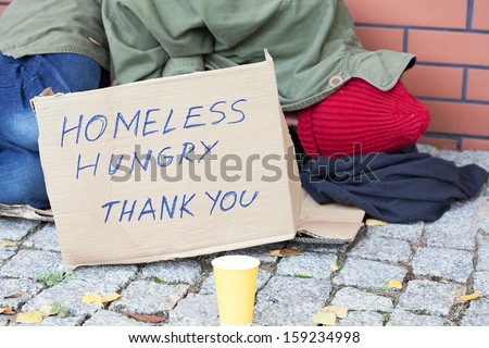 Homeless hungry poor man sleeping on a street - stock photo