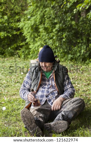 Homeless leaning against garbage bin in the park - stock photo