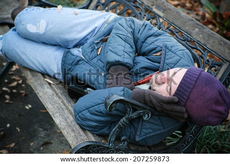 Homeless man asleep on a park bench with a bottle of wine.