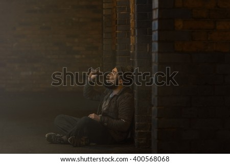 homeless man drinking alcohol on the backstreet