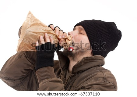 Homeless man holding a bottle of alcohol - stock photo