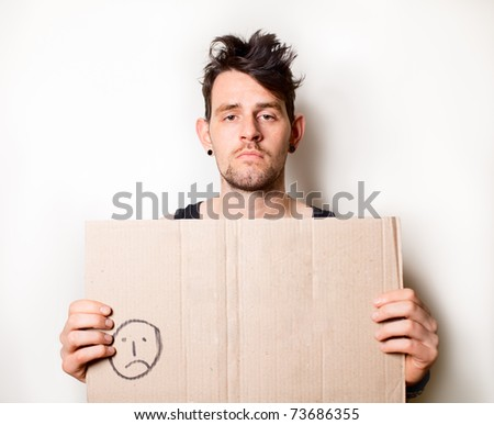 Homeless man holding blank cardboard sign - stock photo