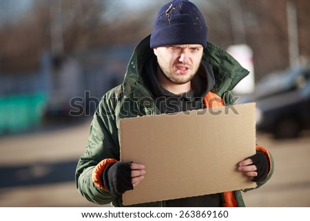 Homeless man holds blank cardboard for your own text - stock photo