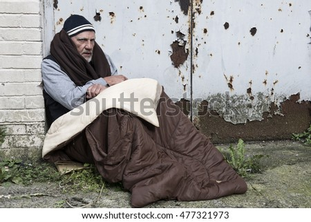 Homeless man in an old sleeping bag resting against a rusty door.