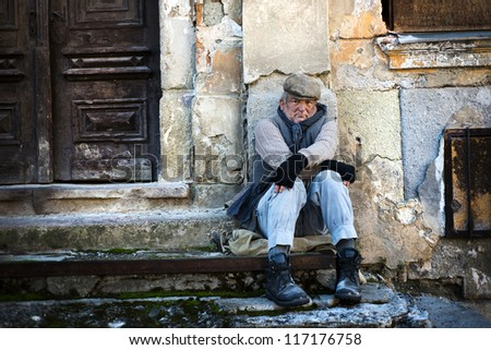 Homeless man in the street is being cold - stock photo