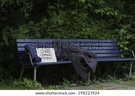 Homeless man on a park bench with a cardboard sign