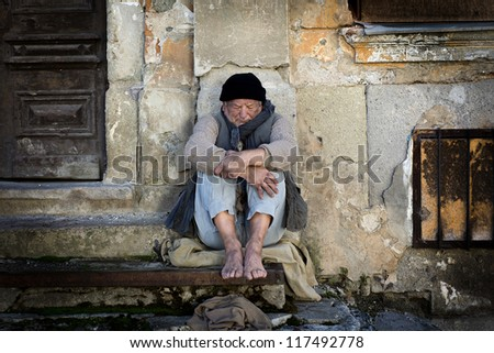 Homeless man on the street is being cold - stock photo