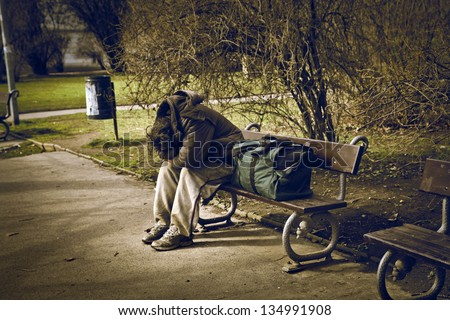 homeless man sitting on a bench in a park - stock photo