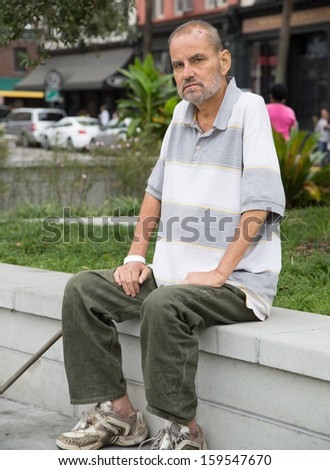 Homeless man sitting outdoors during the daytime - stock photo