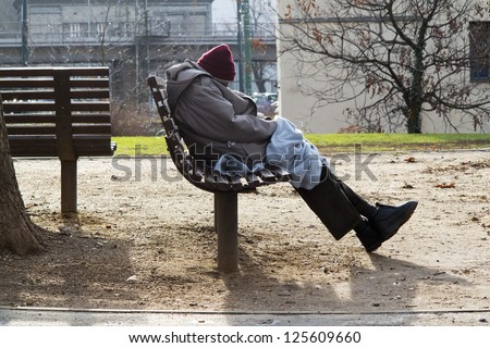 homeless man sleeping on a bench in a one-way street - stock photo