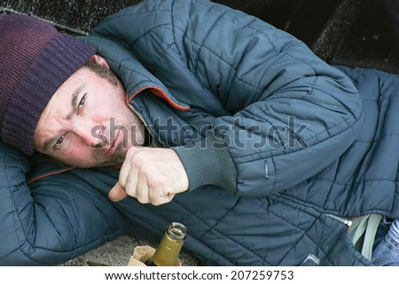Homeless man sleeping on the ground in the cold with a cough.