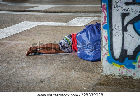 Homeless man sleeps under overpass. - stock photo